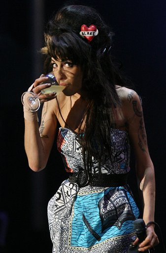 Jazz Soul diva Amy Winehouse, from England, has a drink while performing to ninety thousand spectators on the main stage of the Rock in Rio Lisboa music festival at the Bela Vista Park Friday, May 30, 2008, Portugal. (AP Photo/Steven Governo)