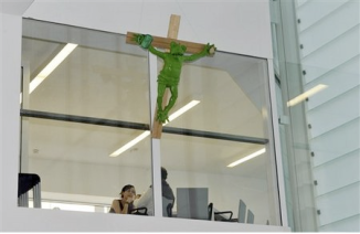"""In this photo taken May 24, 2008 a view of a green frog nailed to a cross outside an office, during a protest inside the """"Museion"""" museum in Bolzano , northern Italy. Museum officials said Thursday Aug. 28, 2008 the sculpture that has angered Pope Benedict XVI and local officials will continue to be on display. The board of the foundation of the """"Museion"""", voted to keep the work by the late German artist Martin Kippenberger, the museum said in a statement. Earlier in August the pope had written a letter to Franz Pahl, the president of the Trentino-Alto Adige region that includes Bolzano, denouncing the sculpture. """"(It) has offended the religious feelings of many people who consider the cross a symbol of God's love and of our redemption,"""" (AP Photo/Othmar Seehauser)"""