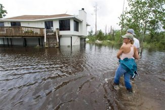 Lisa and Cliff Lyons stand in the flooded yard in front of their home in Coin du Lestin Estates that was flooded in the aftermath of Hurricane Gustav Tuesday, Sept. 2, 2008, in Slidell, La. (AP Photo/Houston Chronicle, Brett Coomer)