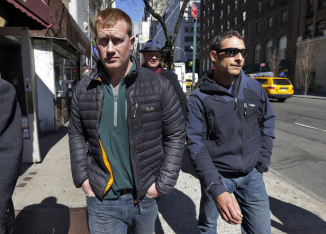 James Brady, left, and Andrew Rossig, right, two parachutists who BASE jumped from One World Trader Center in September 2013, are accompanied by attorney Timothy Parlatore to surrender to police, in New York, Monday, March 24, 2014. (Richard Drew | The Associated Press)